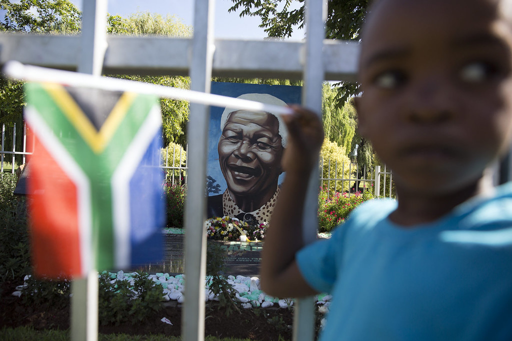 . A boy plays with a South African national flag in front of a mural of Nelson Mandela in Soweto Township, as the funeral of former South African President takes place in Qunu, on December 15, 2013 in Soweto, South Africa. Mr Mandela passed away on the evening of December 5, 2013 at his home in Houghton at the age of 95. Mandela became South Africa\'s first black president in 1994 after spending 27 years in jail for his activism against apartheid in a racially-divided South Africa.  (Photo by Oli Scarff/Getty Images)
