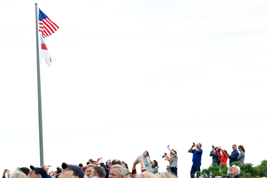 . Spectators watch as former U.S. President George H.W. Bush and Mike Elliott, US Army Sergeant 1st Class (ret), jump out of a helicopter and parachute down to St. Anne\'s Episcopal Church on June 12, 2014 in Kennebunkport, Maine. The President is celebrating his 90th birthday today.   (Photo by Eric Shea/Getty Images)