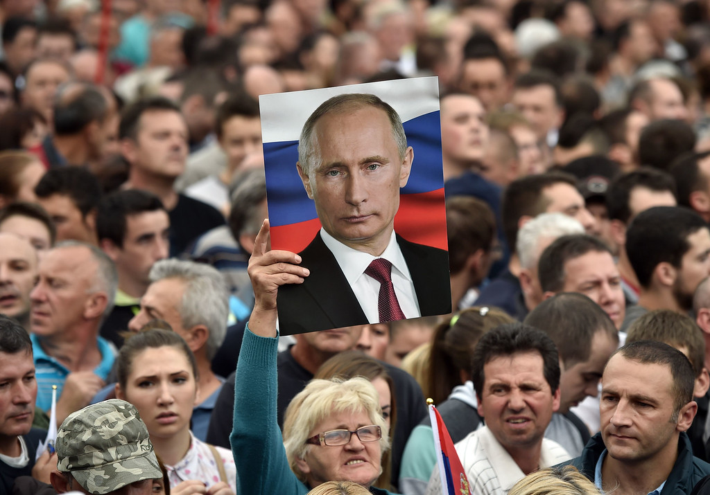 . A spectator holds a poster showing Russian President Vladimir Putin ahead of a military parade in Belgrade on October 16, 2014. ANDREJ ISAKOVIC/AFP/Getty Images