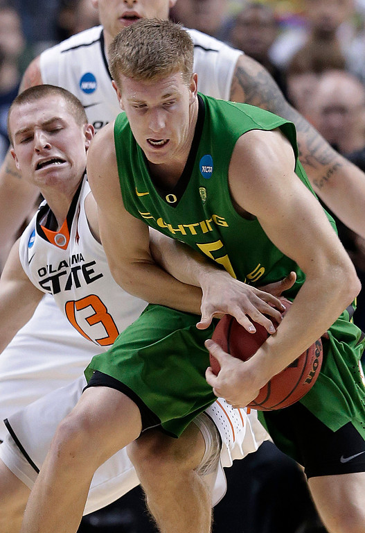 . Oklahoma State guard Phil Forte, left, reaches for the ball in between the arms of Oregon forward E.J. Singler during the first half of a second-round game in the NCAA college basketball tournament in San Jose, Calif., Thursday, March 21, 2013. (AP Photo/Jeff Chiu)