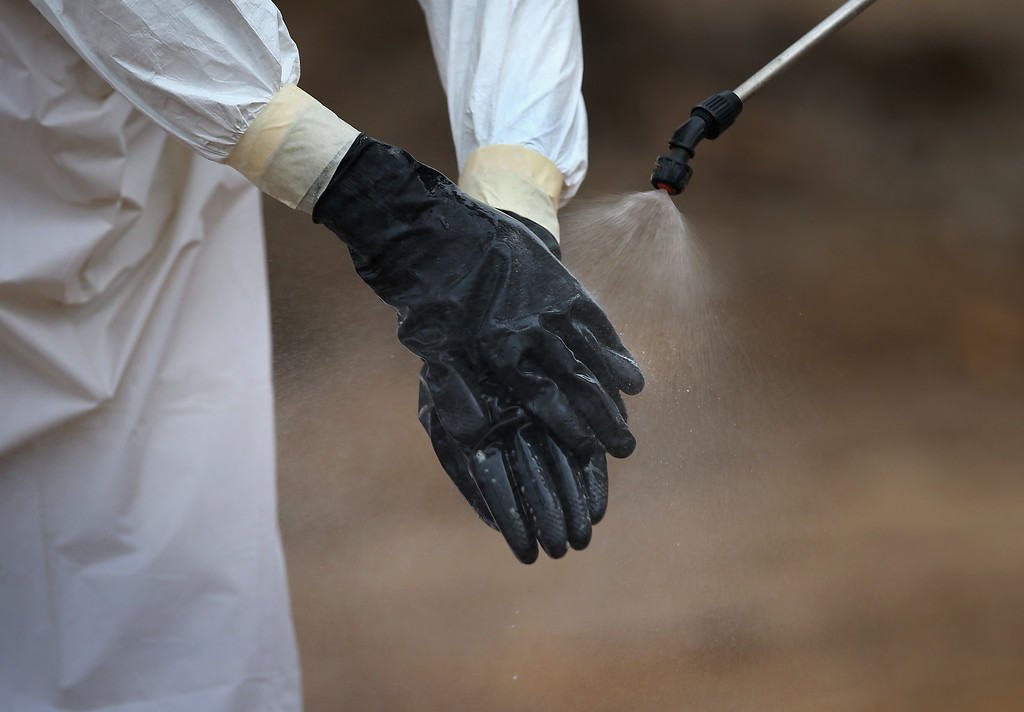 ". A burial team member wearing personal protective equipment (PPE), is decontaminated at the U.S.-built cemetery for ""safe burials\"" on January 27, 2015 in Disco Hill, Liberia. The cemetery, operated by USAID-funded Global Communities, has buried almost 300 people in its first month of operation, with increasingly fewer of the bodies coming from Ebola Treatment Units (ETUs), as infection rates decline. The cemetery, where burial team members wear protective clothing, has been seen in Monrovia as a major achievement, as families of deceased loved ones are permitted to view the burials, important in Liberian culture. In an effort to control the Ebola epidemic in 2014, the Liberian government had ordered the cremation of all deceased in the capital, often further traumatizing surviving family members and unintentionally encouraging many families to hide their dead for secret burials.  (Photo by John Moore/Getty Images)"
