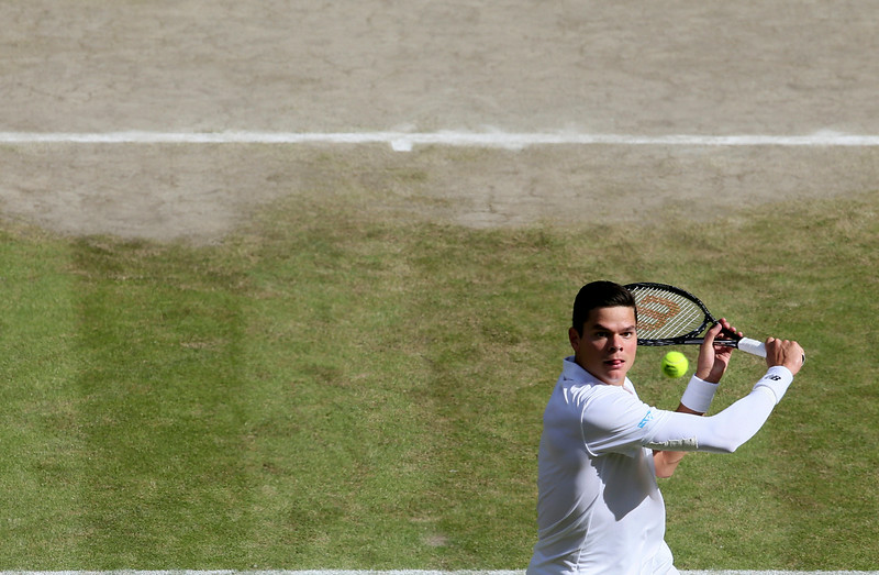 . Milos Raonic of Canada advances to the net to play a return to Roger Federer of Switzerland during their men�s singles semifinal match at the All England Lawn Tennis Championships at Wimbledon, London, Friday, July, 4, 2014. (AP Photo/John Walton, Pool)