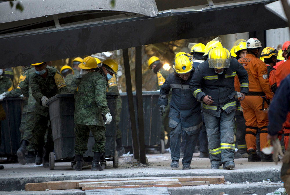 Description of . Mexican soldiers and firefighters remove debris from the headquarters of the state-owned Mexican oil giant Pemex in Mexico City on February 1, 2013, following a blast inside the building. An explosion rocked the skyscraper, leaving up to now 25 dead and 100 injured, as a plume of black smoke billowed from the 54-floor tower, according to official sources.  AFP PHOTO/ YURI CORTEZ/AFP/Getty Images