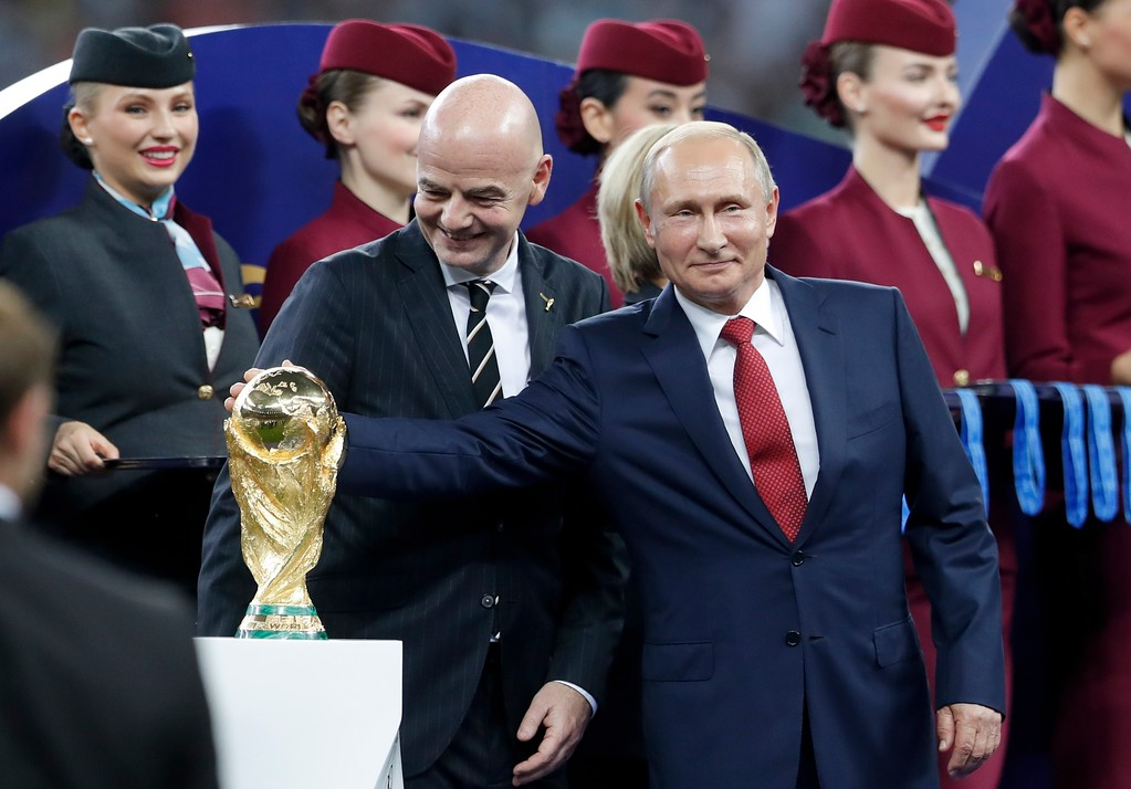 . Russian President Vladimir Putin touches the World Cup trophy as FIFA President Gianni Infantino stands beside him, at the end of the final match between France and Croatia at the 2018 soccer World Cup in the Luzhniki Stadium in Moscow, Russia, Sunday, July 15, 2018. France won 4-2. (AP Photo/Petr David Josek)