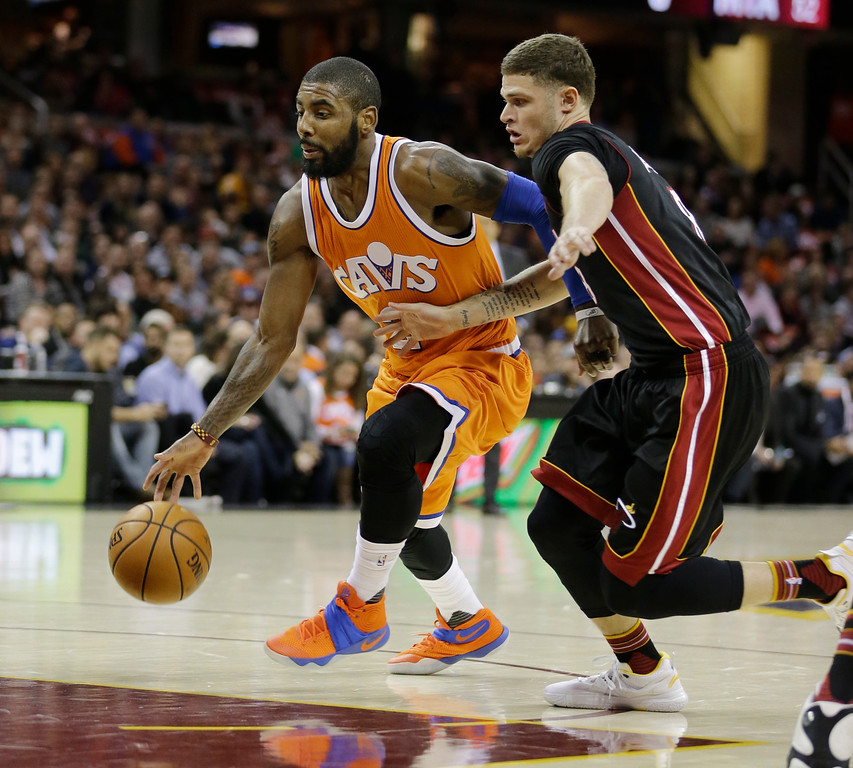 . Cleveland Cavaliers\' Kyrie Irving (2) drives past Miami Heat\'s Tyler Johnson (8) in the first half of an NBA basketball game Friday, Dec. 9, 2016, in Cleveland. (AP Photo/Tony Dejak)