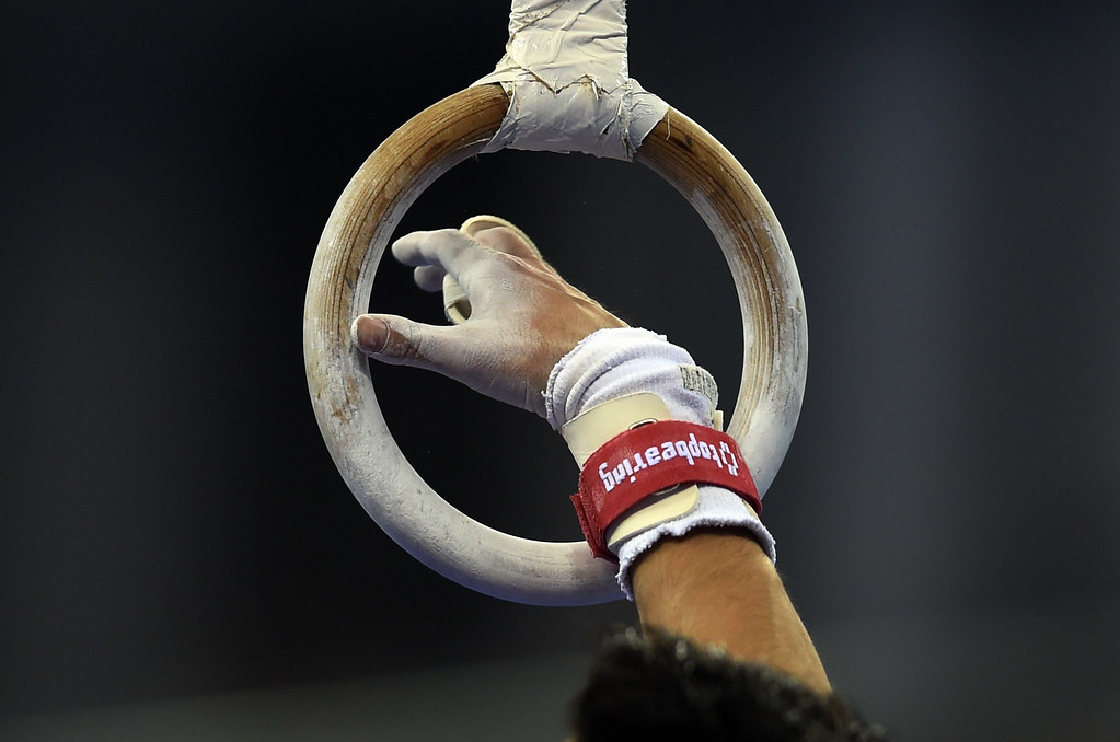 . China\'s Deng Shudi grabs the rings during the men\'s qualification at the Gymnastics World Championships in Nanning, in China\'s southern Guangxi province on October 3, 2014. GREG BAKER/AFP/Getty Images