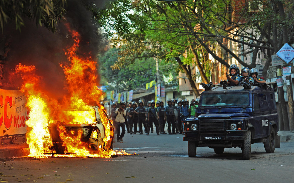 . A car stands in flames after activists of the opposition Bangladesh Nationalist Party (BNP) set it on fire during a protest in Dhaka, Bangladesh, Saturday, March 2, 2013. Demonstrators protesting the death penalty given to Delwar Hossain Sayedee, one of the top leaders of the country\'s largest Islamic party Jamaat-e-Islami, clashed with Bangladeshi security forces for a third straight day on Saturday, killing two people and injuring about a dozen, police said. (AP Photo)