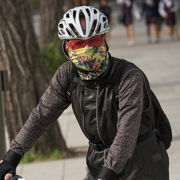Person wearing a mask and helmet riding bicycle, Seoul, South Korea