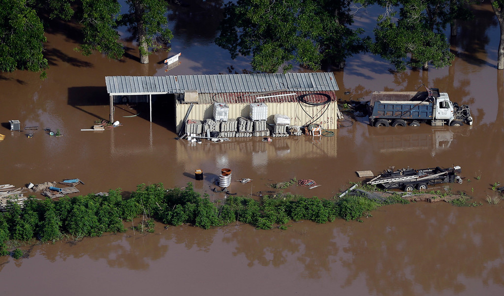 . In this aerial photo, a building and dump truck are surrounded by floodwaters near the Brazos River Saturday, May 30, 2015, in Rosenberg, Texas. The Colorado River in Wharton and the Brazos and San Jacinto rivers near Houston are the main focus of concern as floodwaters moved from North and Central Texas downstream toward the Gulf of Mexico. (AP Photo/David J. Phillip)
