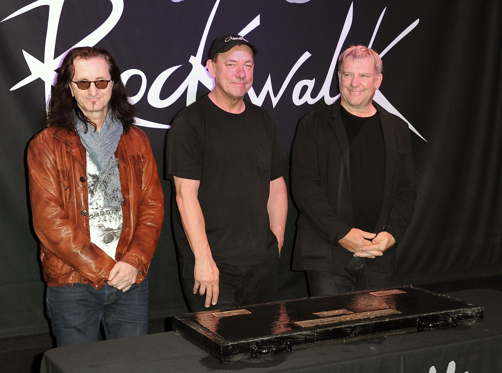 ". This Nov. 20, 2012 file photo shows members of the band Rush, from left, Geddy Lee, Neil Peart, and Alex Lifeson at the RockWalk induction of Rush at Guitar Center in Los Angeles. The eclectic group of rockers Rush and Heart, rappers Public Enemy, songwriter Randy Newman, ""Queen of Disco\"" Donna Summer and bluesman Albert King will be inducted into the Rock and Roll Hall of Fame next April in Los Angeles. The inductees were announced Tuesday by 2012 inductee Flea of The Red Hot Chili Peppers at a news conference in Los Angeles. (Photo by Richard Shotwell/Invision/AP, file)"