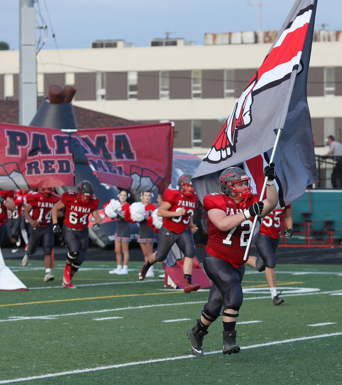. Randy Meyers - The Morning Journal<br> Parma senior Ryan Madison leads the team onto the field against Bay on Sept. 13.