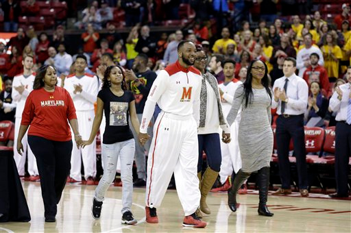 . Maryland guard/forward Dez Wells, center, leads family members onto the court during a senior day ceremony before an NCAA college basketball game against Michigan, Saturday, Feb. 28, 2015, in College Park, Md. (AP Photo/Patrick Semansky)