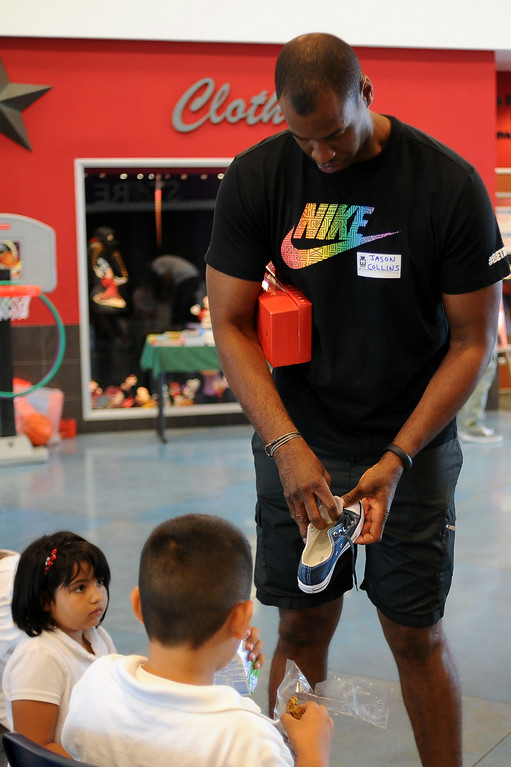. NBA player Jason Collins helps children with shoes during MEND�s (Meet Each Need with Dignity) 13th annual �Head to Toes,� program at the Pacoima charity�s center Wednesday, August 27, 2014. 240 third-graders from Pacoima�s Vaughn Next Century Learning Center were provided with full back-to-school care: free dental and vision screenings through a healthcare initiative with Verizon Foundation, new shoes and new backpacks chock-full of school supplies school supplies donated by the Ella Fitzgerald Charitable Foundation. (Photo by Hans Gutknecht/Los Angeles Daily News)