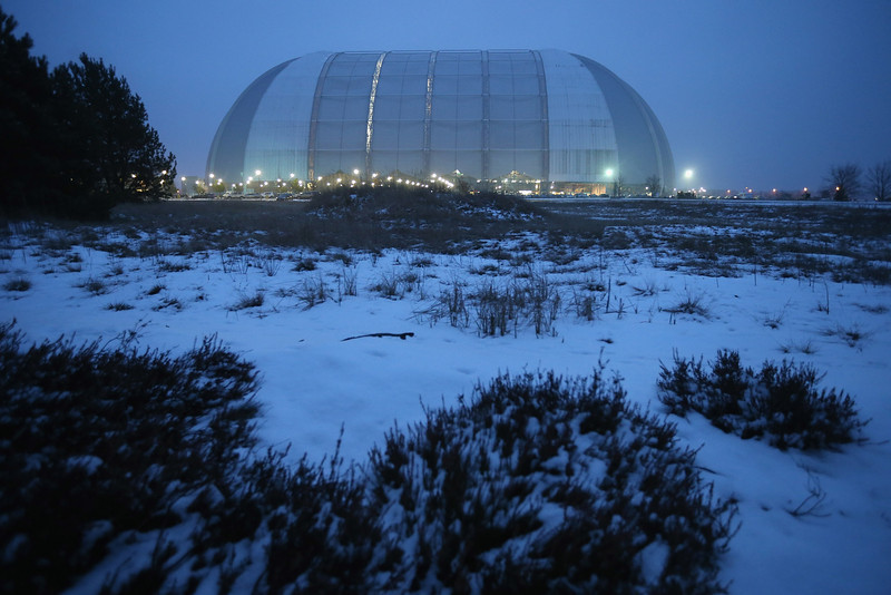 . Evening descends on the snow-covered surroundings of the giant hangar that contains the Tropical Islands indoor resort on February 15, 2013 in Krausnick, Germany. Located on the site of a former Soviet military air base, the resort occupies a hangar built originally to house airships designed to haul long-distance cargo. Tropical Islands opened to the public in 2004 and offers visitors a tropical getaway complete with exotic flora and fauna, a beach, lagoon, restaurants, water slide, evening shows, sauna, adventure park and overnights stays ranging from rudimentary to luxury. The hangar, which is 360 metres long, 210 metres wide and 107 metres high, is tall enough to enclose the Statue of Liberty.  (Photo by Sean Gallup/Getty Images)