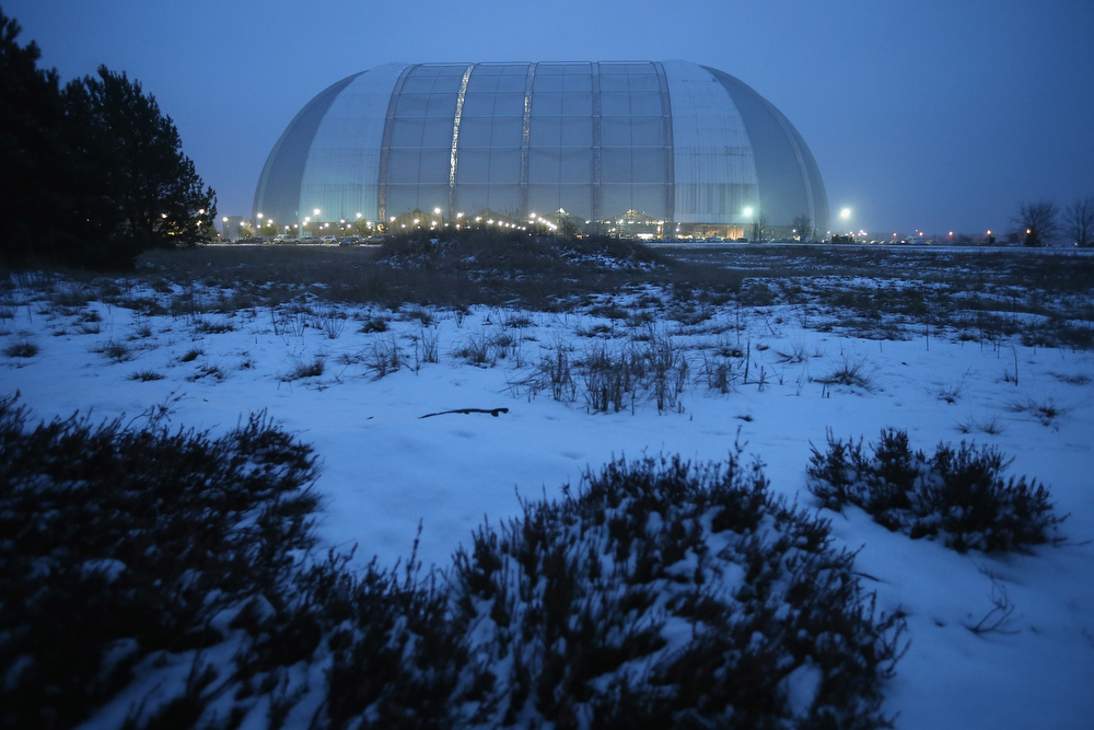 Description of . Evening descends on the snow-covered surroundings of the giant hangar that contains the Tropical Islands indoor resort on February 15, 2013 in Krausnick, Germany. Located on the site of a former Soviet military air base, the resort occupies a hangar built originally to house airships designed to haul long-distance cargo. Tropical Islands opened to the public in 2004 and offers visitors a tropical getaway complete with exotic flora and fauna, a beach, lagoon, restaurants, water slide, evening shows, sauna, adventure park and overnights stays ranging from rudimentary to luxury. The hangar, which is 360 metres long, 210 metres wide and 107 metres high, is tall enough to enclose the Statue of Liberty.  (Photo by Sean Gallup/Getty Images)