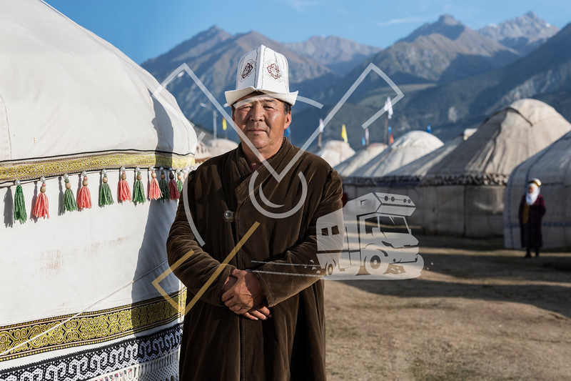 Kyrgyz man wearing a Kalpak stands next to his yurt at the World Nomad Games 2018 yurt camp