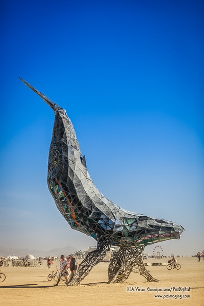 The Space Whale is a 50 foot tall full-scale crystalline humpback whale mother and calf diving through the sky built from steel and stained glass.