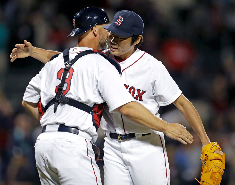 . Boston Red Sox catcher David Ross (3) hugs relief pitcher Koji Uehara at the end of an exhibition baseball game against the Minnesota Twins in Fort Myers, Fla., Thursday, March 27,  2014. The Red Sox won 4-1. (AP Photo/Gerald Herbert)