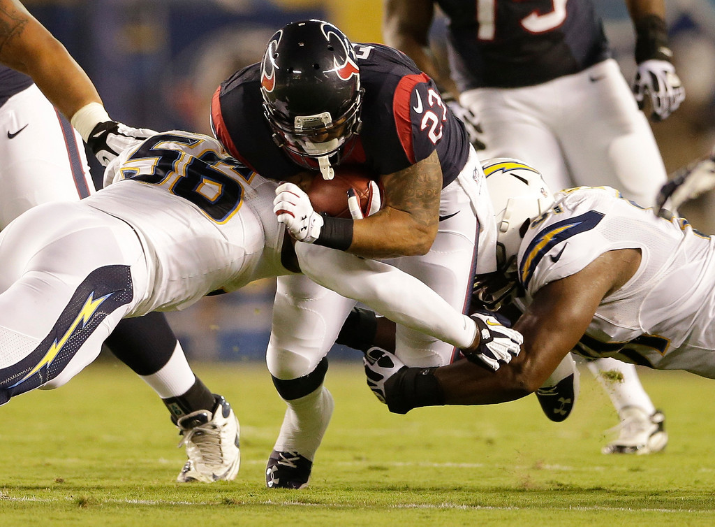 . Houston Texans running back Arian Foster drives between San Diego Chargers inside linebacker Donald Butler, left, and defensive end Kendall Reyes during the first half of an NFL football game Monday, Sept. 9, 2013, in San Diego. (AP Photo/Gregory Bull)