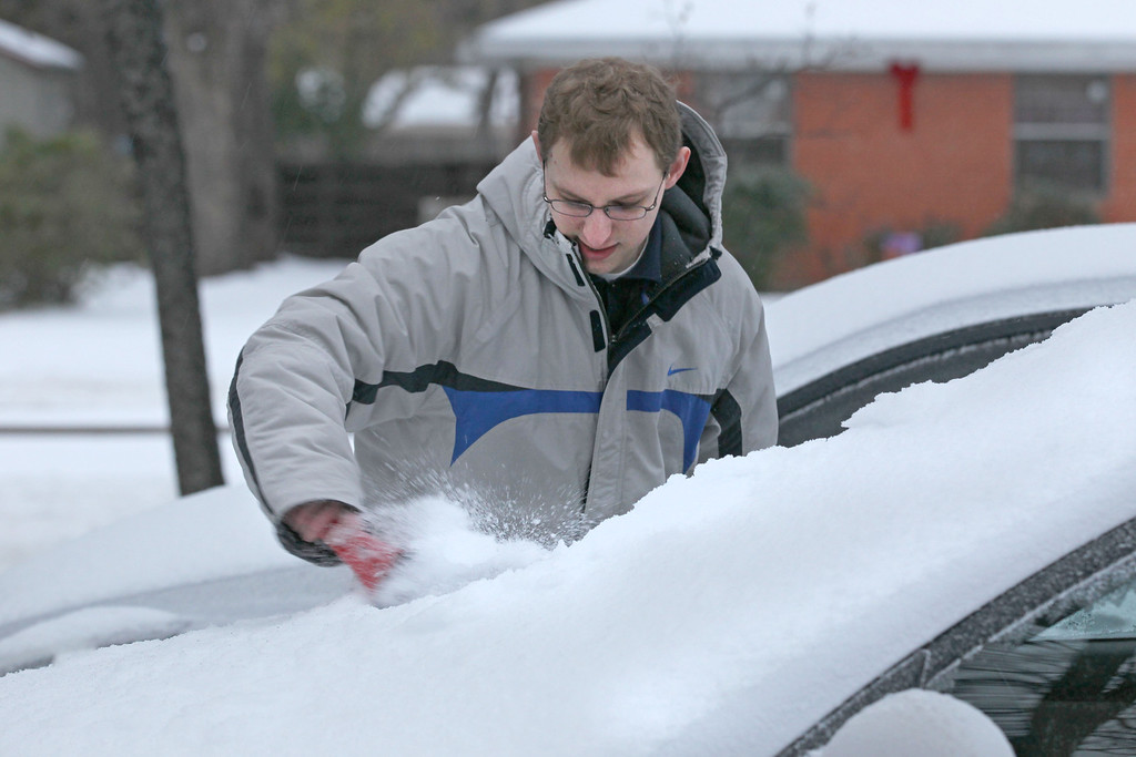 . Daniel Poma of Denton scrapes ice off his car before trying to take his finance to work in Hurst, Texas following an overnight ice storm on Friday, Dec. 6, 2013.  (AP Photo/The Dallas Morning News, Gary Barber)