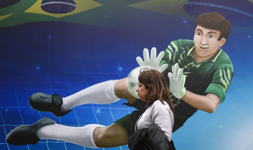 . A morning commuter walks past a mural depicting a goalkeeper in Sao Paulo on June 11, 2014. Brazil\'s largest city and cars are decorated with murals and flags as they prepare to host the opening match of the FIFA 2014 World Cup between Brazil and Croatia on June 12th.   AFP PHOTO/ ODD ANDERSEN/AFP/Getty Images