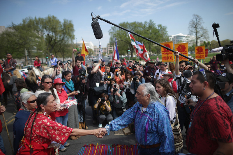 ". Casey Camp of the Ponca Nation (L) shakes hands with Piscataway Indian Nation Chief Billy Redwing Tayac during a traditional opening ceremony to begin a demonstration against the proposed Keystone XL pipeline at the U.S. Capitol Reflecting Pool on the National Mall April 22, 2014 in Washington, DC. As part of its ""Reject and Protect\"" protest, the Cowboy and Indian Alliance is organizing a weeklong series of actions by farmers, ranchers and tribes to show their opposition to the pipeline.  (Photo by Chip Somodevilla/Getty Images)"