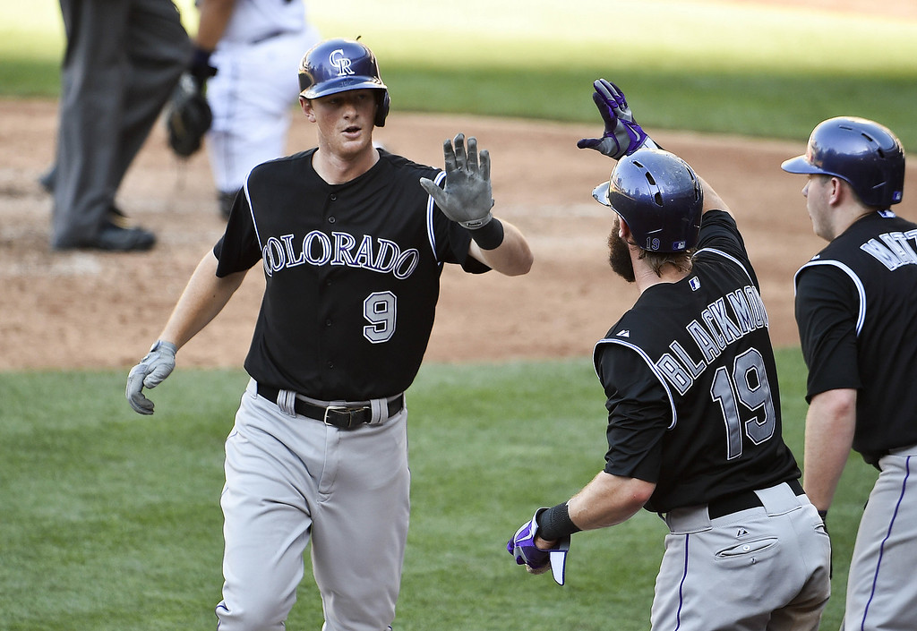 . SAN DIEGO, CA - AUGUST 13:  DJ LeMahieu (L) #9 of the Colorado Rockies is congratulated by Charlie Blackmon #19 after hitting a solo home run during the fifth inning of a baseball game against the San Diego Padres at Petco Park on August 13, 2014 in San Diego, California.  (Photo by Denis Poroy/Getty Images)