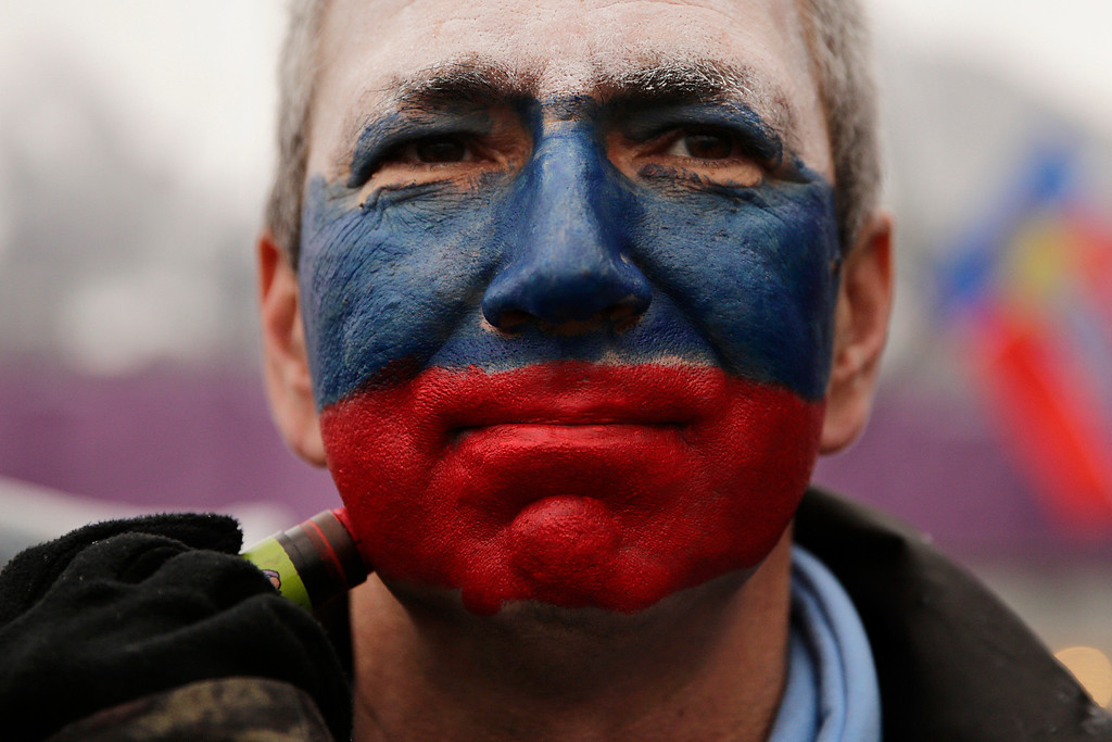 . Kamil Aizetulin gets his face painted in the colors of the Russian flag during a women\'s ski cross seeding run at the Rosa Khutor Extreme Park, the 2014 Winter Olympics, Friday, Feb. 21, 2014, in Krasnaya Polyana, Russia. (AP Photo/Jae C. Hong)