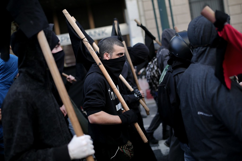 . Masked protesters hold black flags as they march in Athens on December 6, 2014, during a protest to commemorate the six-year anniversary of the fatal shooting of teenager Alexis Grigoropoulos by a police officer, an event that plunged Greece into weeks of youth riots. AFP PHOTO / ANGELOS  TZORTZINIS/AFP/Getty Images