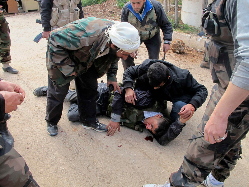 . A bleeding Free Syrian Army fighter is comforted by his comrades as he lies on the ground in Khan al-Assal area, near Aleppo April 20, 2013. Picture taken April 20, 2013. REUTERS/Abdalghne Karoof