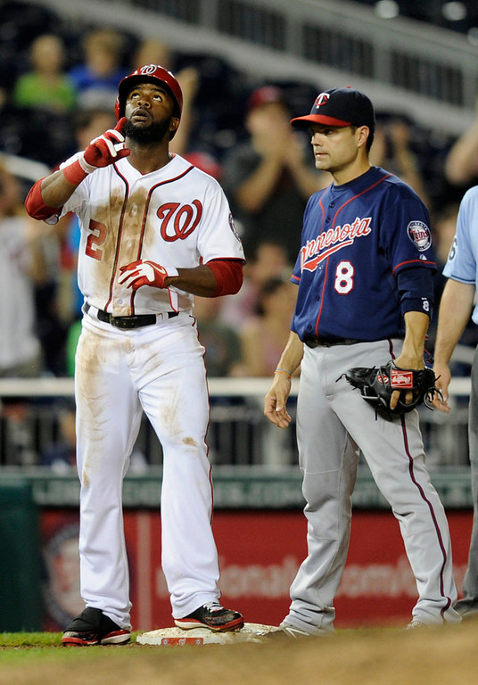 . Washington Nationals\' Denard Span (2) gestures after he tripled during the sixth inning of the second baseball game of a day-night interleague doubleheader as he stands next to Minnesota Twins third baseman Jamey Carroll (8), Sunday, June 9, 2013, in Washington. (AP Photo/Nick Wass)
