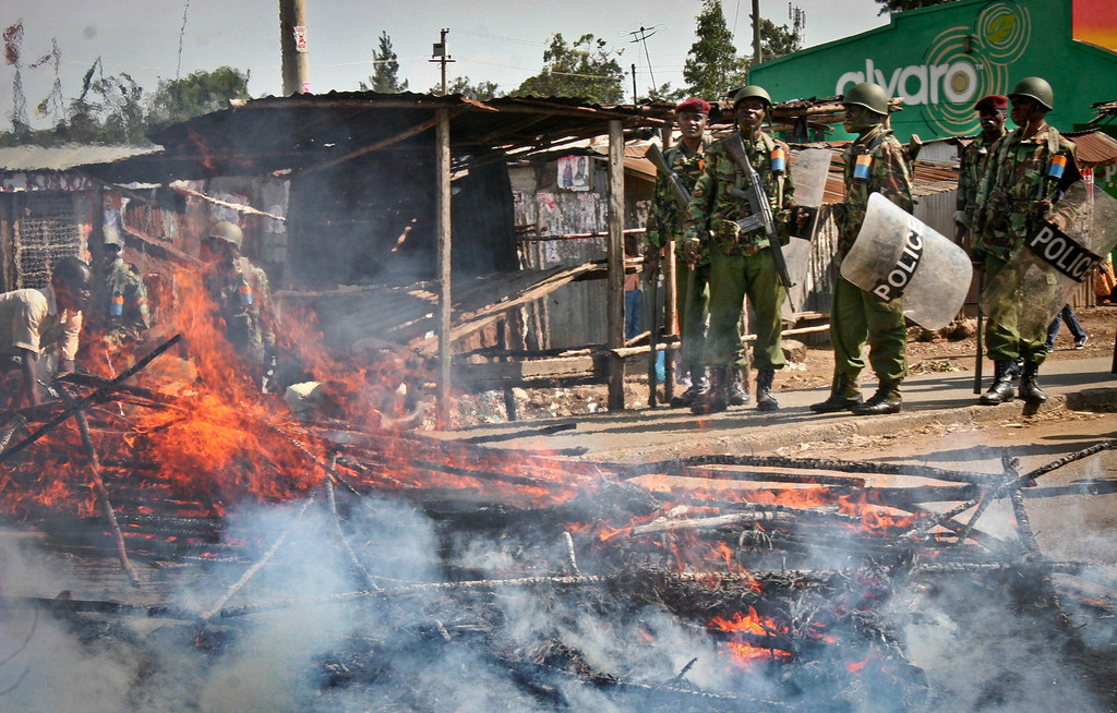 . Police officers with the General Service Unit stand by a burning roadblock set up by protesting supporters of Kenyan presidential candidate Raila Odinga, shortly after the announcement that his opponent Uhuru Kenyatta had won the presidential election, in Kisumu, Kenya Saturday, March 9, 2013.  Uhuru Kenyatta - the son of Kenya\'s founding father and a man accused by an international court of helping orchestrate the vicious violence that marred the nation\'s last vote - was certified as the winner on Saturday of Kenya\'s presidential election by the slimmest majority - 50.07 percent. (AP Photo)