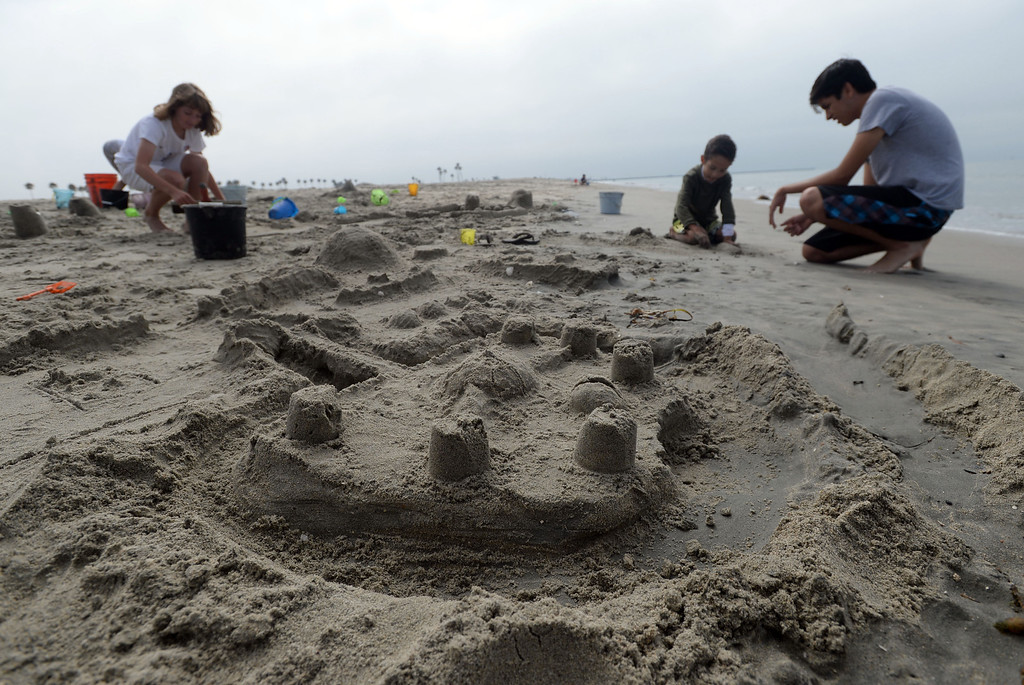 . Children had a chance to hone their sand castle building skills in a sand castle camp Monday at Granada Beach in Belmont Shore. Camp counselor John Williams helps William De Baca with his castle. 20130805 Photo by Steve McCrank / Staff Photographer