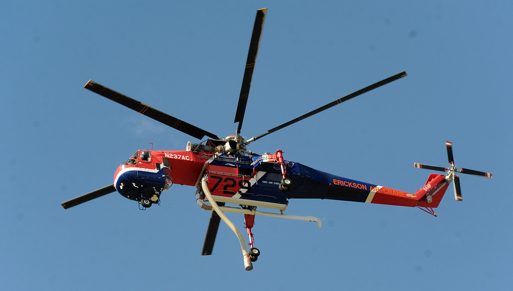 . A Erickson Air-Crane flies after making a drop as Los Angeles County Firefirghters with aid of water dropping helicopters battle a five acre brush fire in the San Gabriel Mountains above Azusa just above the former Shooting range on Tuesday, Aug. 27, 2013 in Azusa, Calif.   (Keith Birmingham/Pasadena Star-News)