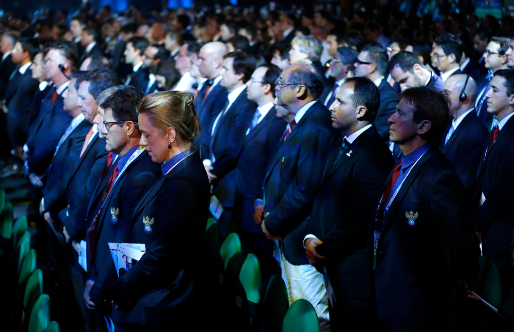 . Delegates stand for a minute of silence for late South African President Nelson Mandela during the draw ceremony for the 2014 soccer World Cup in Costa do Sauipe near Salvador, Brazil, Friday, Dec. 6, 2013. (AP Photo/Victor R. Caivano)
