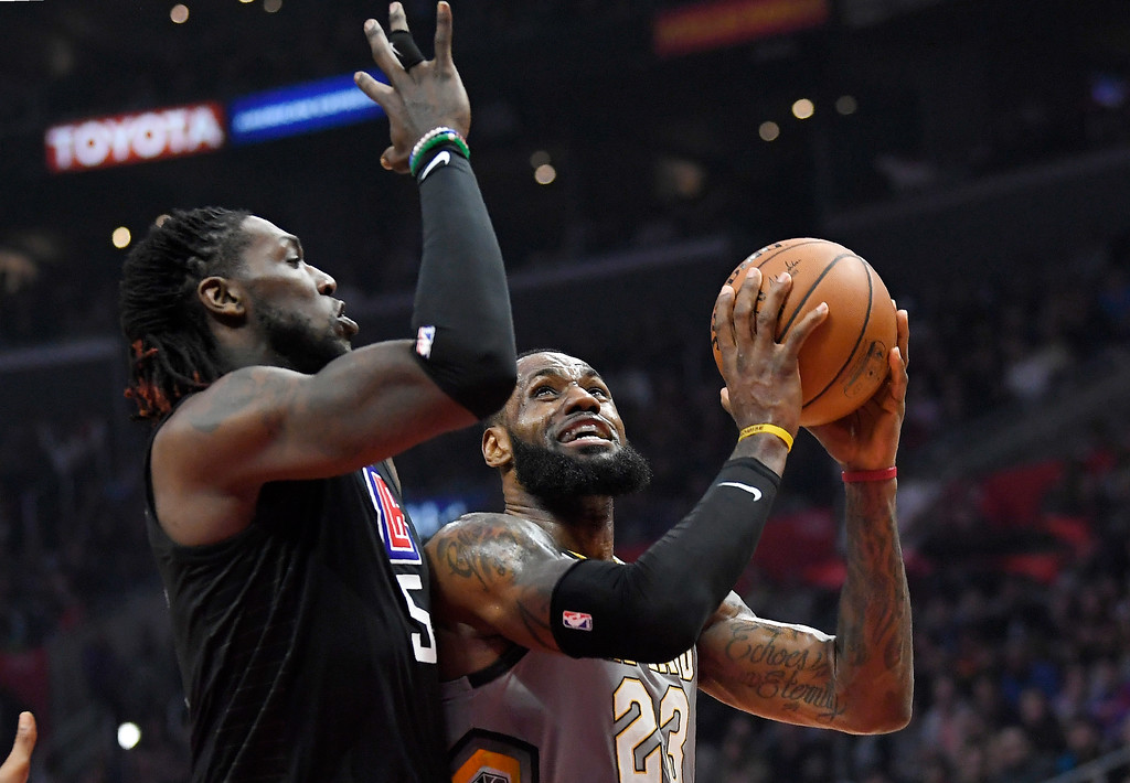 . Cleveland Cavaliers forward LeBron James, right, shoots as Los Angeles Clippers forward Montrezl Harrell defends during the first half of an NBA basketball game Friday, March 9, 2018, in Los Angeles. (AP Photo/Mark J. Terrill)