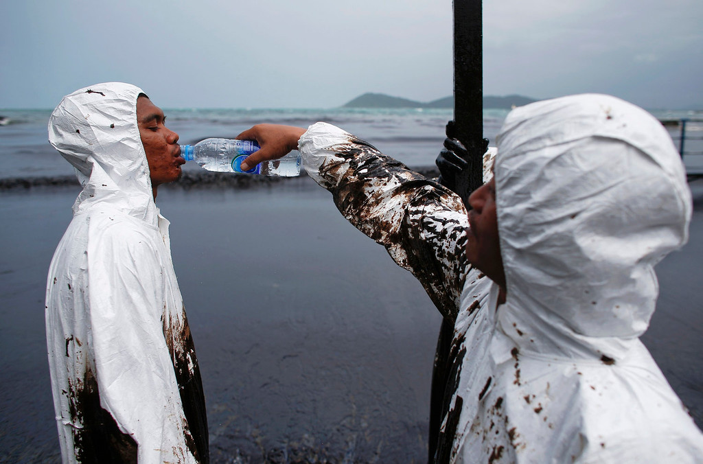 . A Thai soldier in white biohazard suit is fed water as he takes part with others in a clean-up operation at Ao Prao Beach on Koh Samet, Rayong July 30, 2013. Crude oil that leaked from a pipeline in the Gulf of Thailand over the weekend has reached a Thai tourist resort, pipeline operator PTT Global Chemical Pcl said on Monday. Around 50,000 liters of crude oil poured into the sea on Saturday around 20 km (12 miles) off the coast of Rayong, southeast of the capital Bangkok. REUTERS/Athit Perawongmetha
