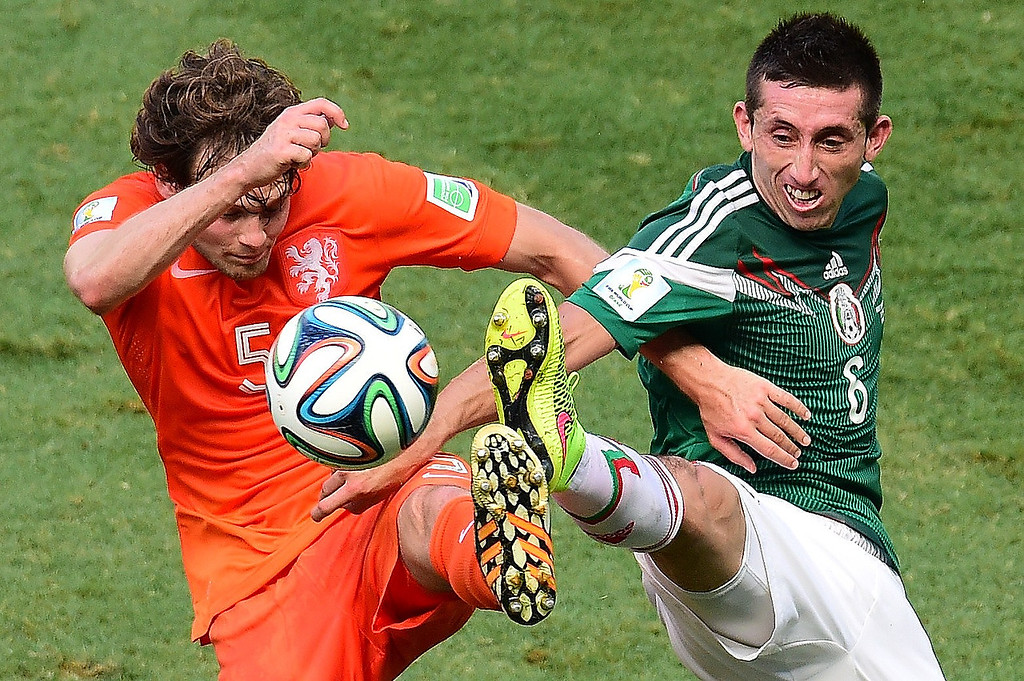 . Netherlands\' defender Daley Blind (L) vies with Mexico\'s midfielder Hector Herrera during a Round of 16 football match between Netherlands and Mexico at Castelao Stadium in Fortaleza during the 2014 FIFA World Cup on June 29, 2014.   JAVIER SORIANO/AFP/Getty Images