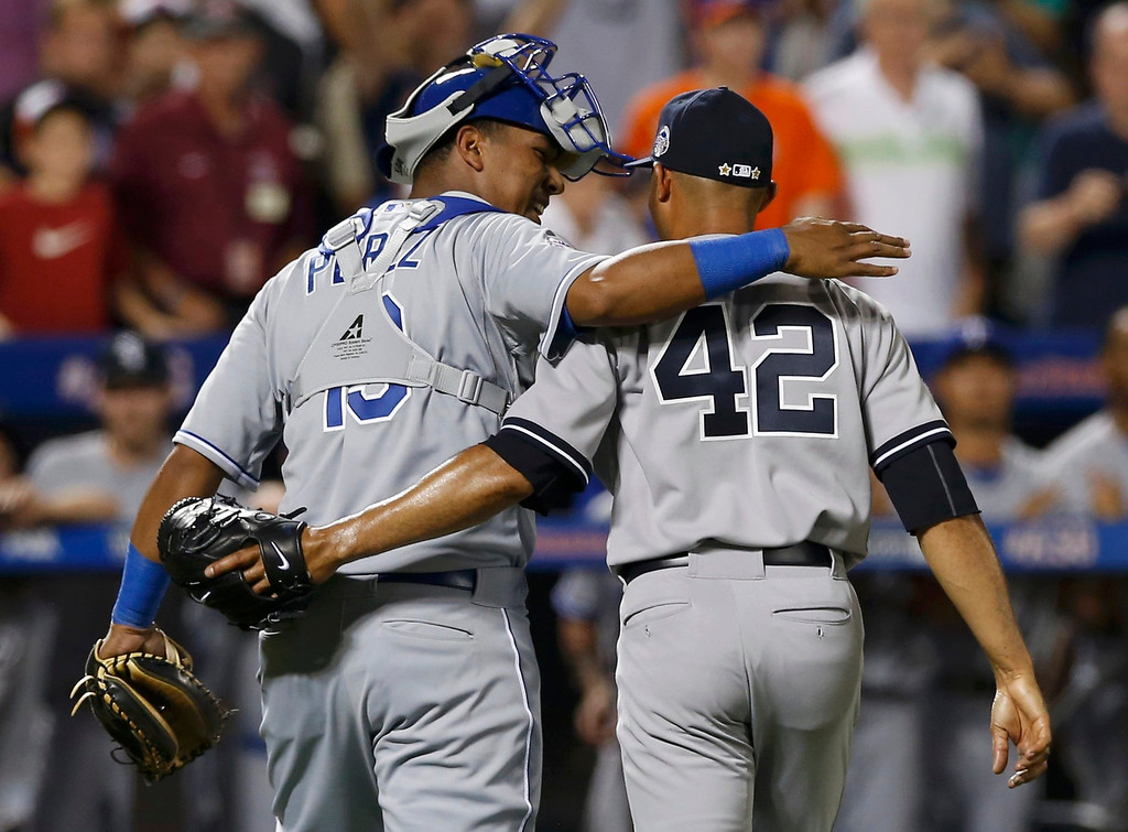 . American League catcher Salvador Perez of the Kansas City Royals hugs New York Yankees pitcher Mariano Rivera after Rivera pitched the eighth inning against the National League during Major League Baseball\'s All-Star Game in New York, July 16, 2013.  REUTERS/Mike Segar