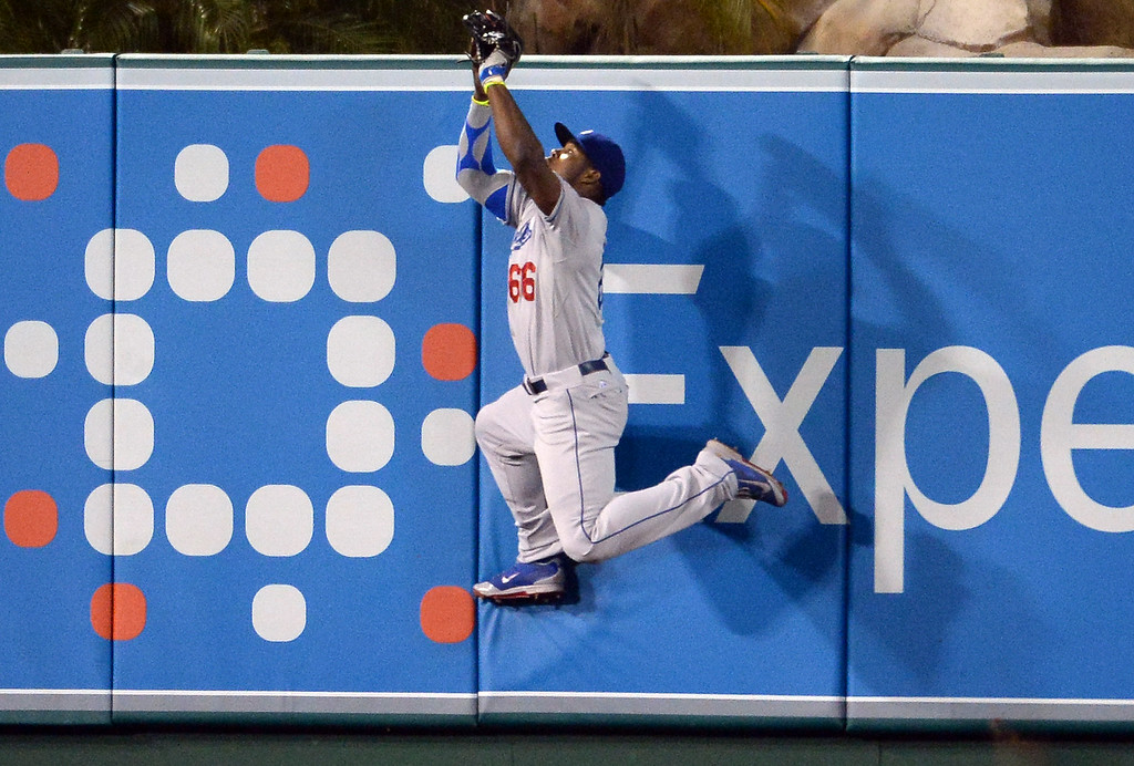 . Los Angeles Dodgers right fielder Yasiel Puig leaps to catch a drive by Los Angeles Angels\' Josh Hamilton (not pictured) in the sixth inning of a baseball game at Anaheim Stadium in Anaheim, Calif., on Thursday, Aug. 7, 2014.  (Photo by Keith Birmingham/ Pasadena Star-News)