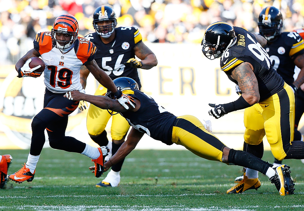 . Brandon Tate #19 of the Cincinnati Bengals avoids a tackle by Ryan Clark #25 of the Pittsburgh Steelers in the first half during the game at Heinz Field on December 23, 2012 in Pittsburgh, Pennsylvania. (Photo by Jared Wickerham/Getty Images)