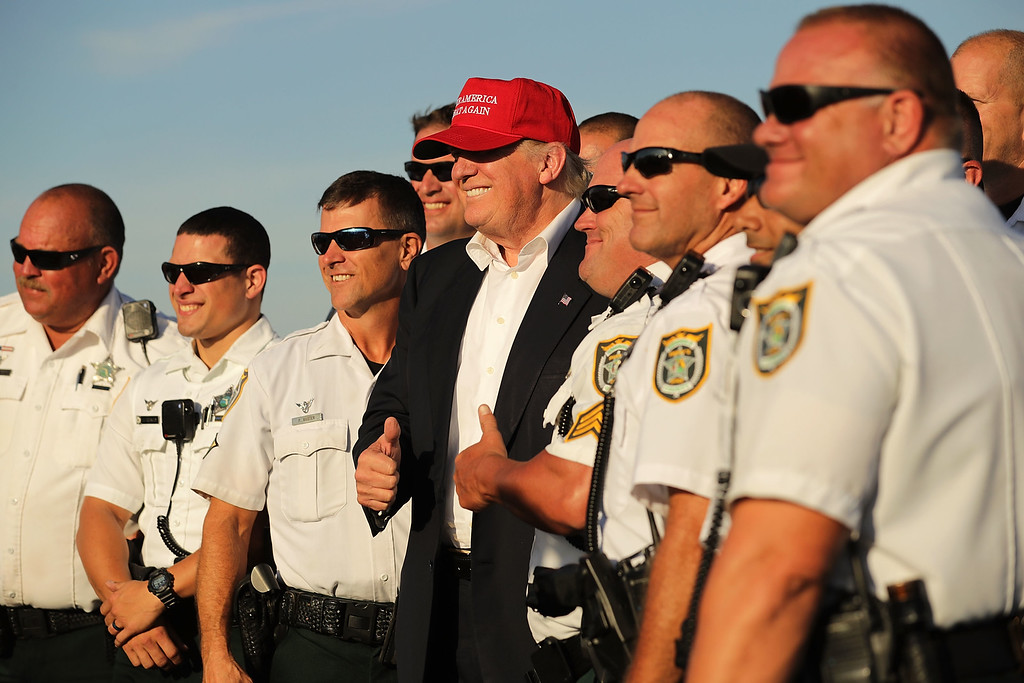 . ORLANDO, FL - NOVEMBER 02:  Republican presidential nominee Donald Trump poses for photographers with law enformcement officers on the tarmac at Orlando International Airport November 2, 2016 in Orlanda, Florida. With less than a week before Election Day in the United States, Trump and his opponent, Democratic presidential nominee Hillary Clinton, are campaigning in key battleground states that each must win to take the White House.  (Photo by Chip Somodevilla/Getty Images)
