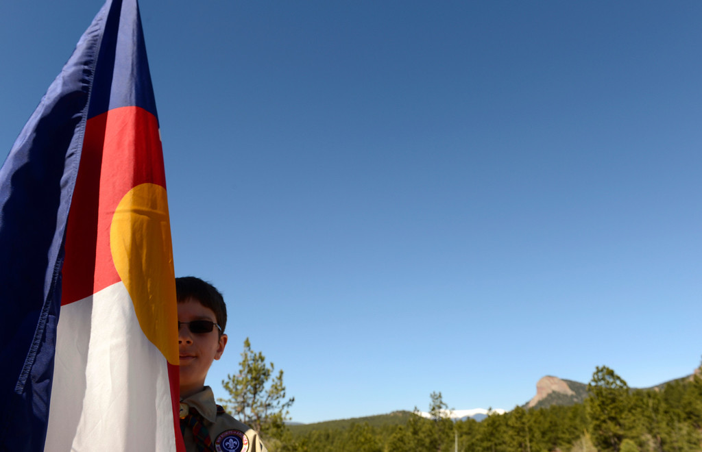 . CONIFER, CO-May 17, 2013: Boy Scout Aiden Boldra, 10, holds the Colorado flag during the dedication of the newest state park, Staunton State Park, May 17, 2013. It has been 27 years since Colorado got a new state park. The park, west of Conifer, will open to the public May 18. (Photo By RJ Sangosti/The Denver Post)