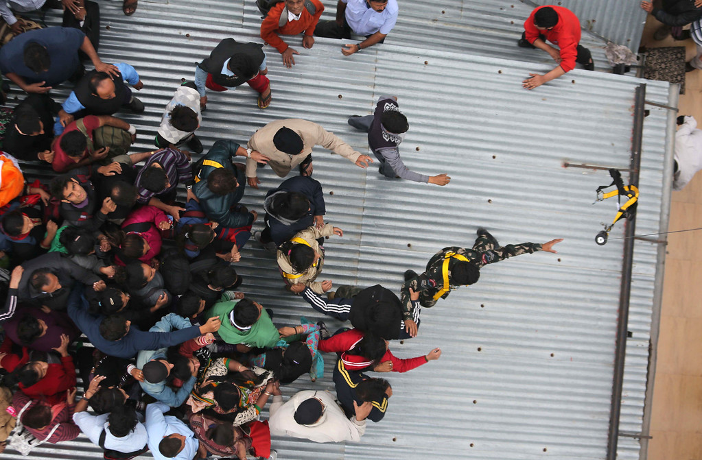 . People stranded on the roof of a five-story hotel rush to be airlifted in Srinagar, India, Tuesday, Sept. 9, 2014. (AP Photo/Dar Yasin)