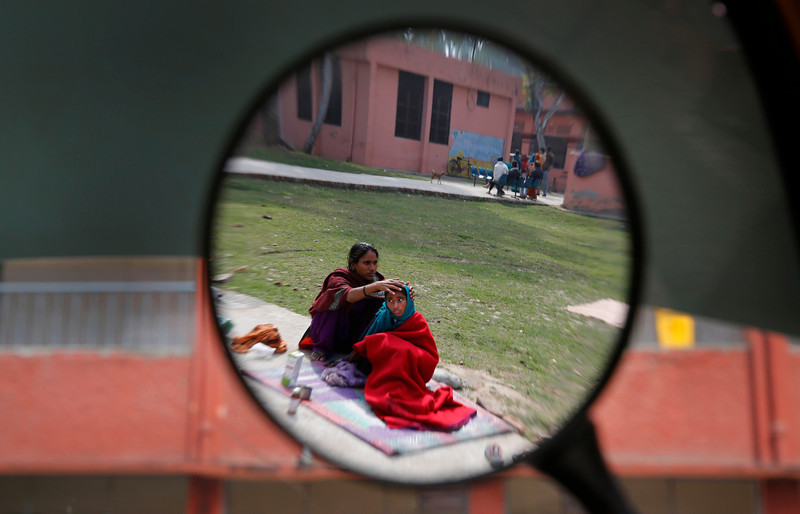 . In this Monday, Feb. 3, 2014 photo, a tuberculosis patient Neha, 11, right, sits in the sun with her mother Jehana as they are reflected in the rear view mirror of a two-wheeler outside Lal Bahadur Shastri Government Hospital at Ram Nagar in Varanasi, India. (AP Photo/Rajesh Kumar Singh)