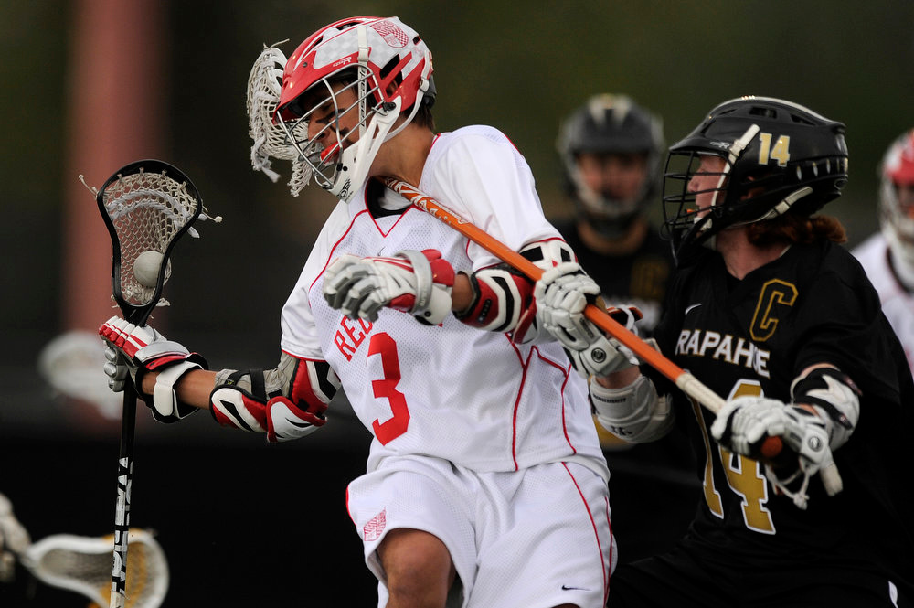 . Regis Jesuit junior midfielder Aaron Horvat #3 takes a stick to the throat from Arapahoe long stick senior midfielder JD Hall #14 during the fourth quarter of the CHSAA 5A boys lacrosse semifinal game on May 15, 2013, at All City Stadium in Denver, Colorado. Arapahoe won 13-5 to advance to the finals. (Photo by Daniel Petty/The Denver Post)