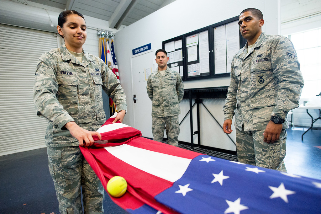 . Staff Sgt. Anahi Ledezma, 26, of Ramona, folds the U.S. flag while steadying a tennis ball during practice at March Air Reserve Base in Riverside, Calif. on Tuesday, May 12, 2015. (Photo by Watchara Phomicinda/ Los Angeles Daily News)