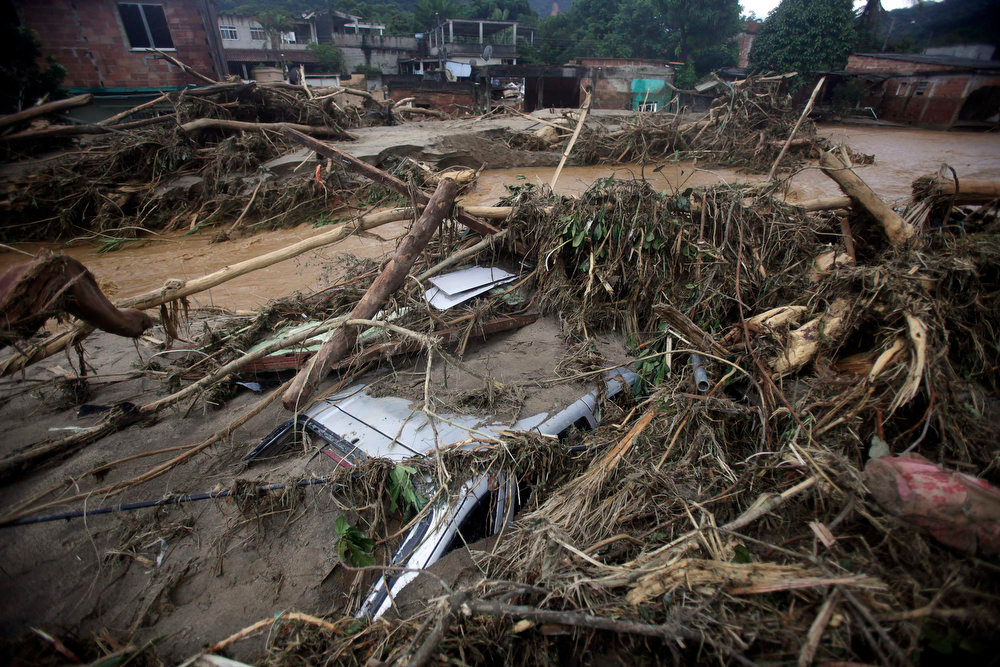Description of . The roof of a damaged car is pictured during the floods of the Capivari river in Xerem, in Duque de Caxias near Rio de Janeiro January 3, 2013.  At least 255 people were dislodged and one person died during the floods of Capivari River in Xerem, a district of Duque de Caxias, local media said. REUTERS/Ricardo Moraes