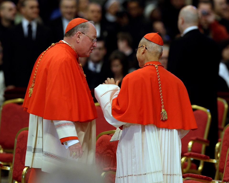 . US Cardinal Timothy Dolan, left, shares a word with Cardinal John Tong Hon, of Hong Kong, as they attend a Mass for the election of a new pope celebrated by Cardinal Angelo Sodano inside St. Peter\'s Basilica, at the Vatican, Tuesday, March 12, 2013. (AP Photo/Andrew Medichini)