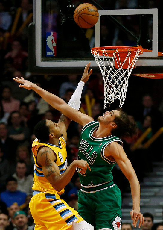 . Denver Nuggets\' Andre Iguodala (L) goes to the basket against Chicago Bulls\' Joakim Noah during the second half of their NBA basketball game in Chicago, Illinois March 18, 2013. REUTERS/Jim Young